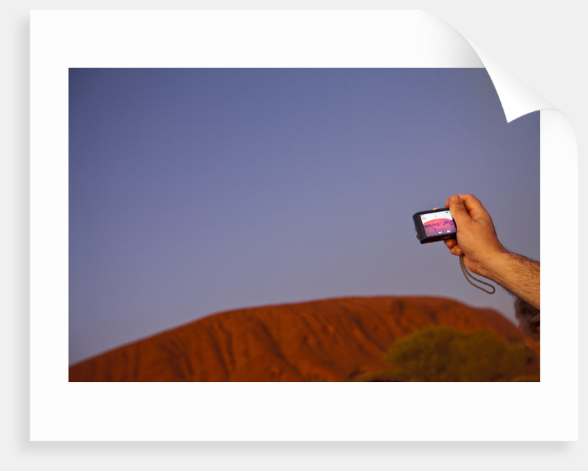 Tourist photographing Ayers Rock in the Australian Outback by Corbis