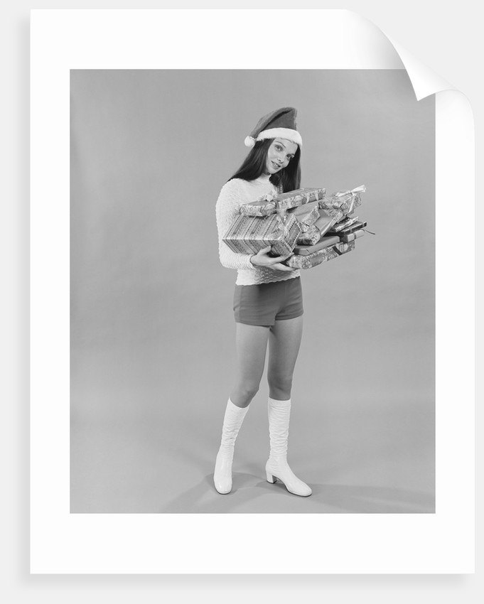 ebb121be3e2e Young woman wearing santa claus hat hot pants go-go boots holding wrapped  christmas presents