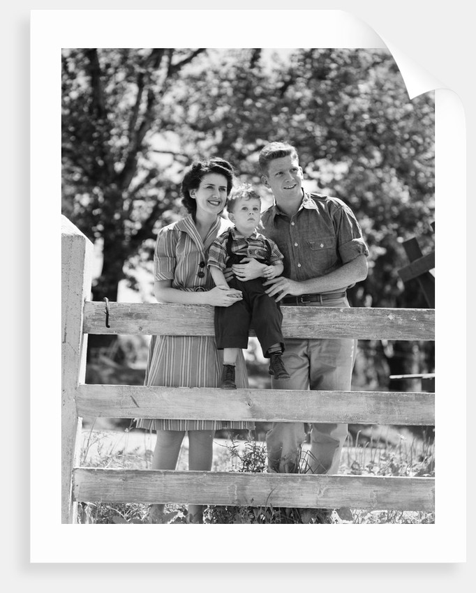 Smiling happy family mother father toddler boy portrait by farm fence by Corbis