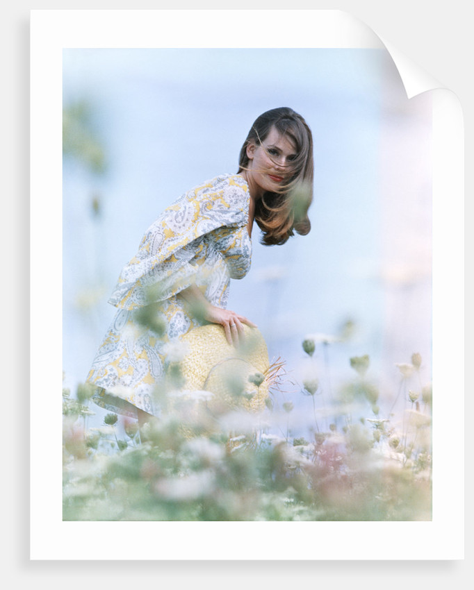 Young woman field of flowers print dress straw hat by Corbis