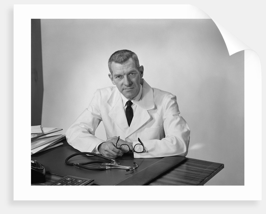 Portrait male doctor sitting at desk serious expression by Corbis