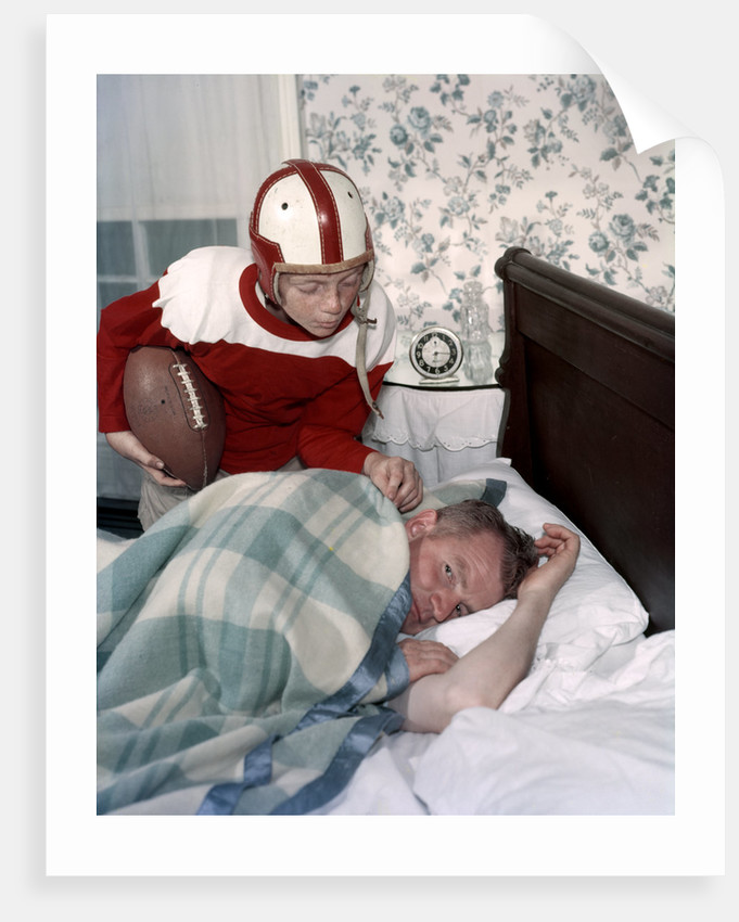 Boy in football uniform waking father asleep in bedroom by Corbis