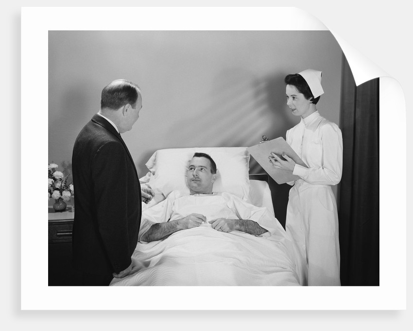 Man doctor woman nurse talking with male patient lying in hospital bed by Corbis