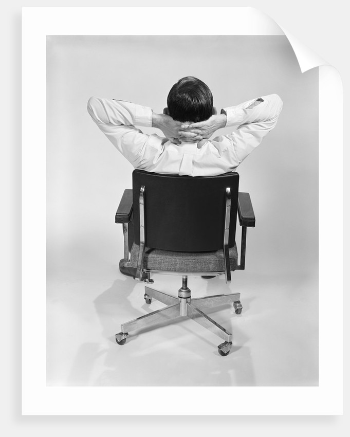 Man from behind sitting in office executive chair hands clasped behind neck by Corbis