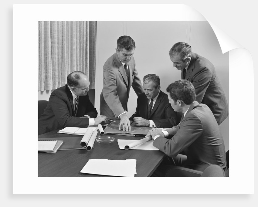 5 executive businessmen at conference table meeting looking over papers & blueprints by Corbis