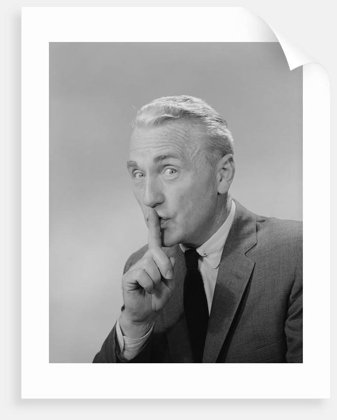 Middle aged man finger to lips making quiet shush sign by Corbis