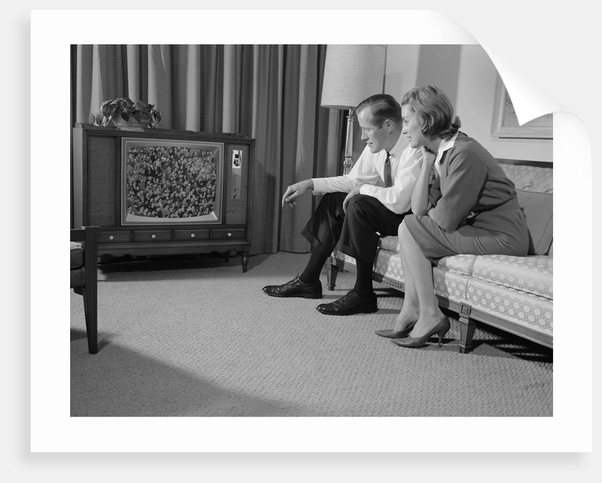 Couple man woman sitting on couch watching television by Corbis