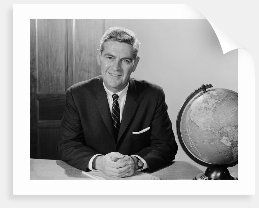 Smiling man sitting at desk with earth globe by Corbis