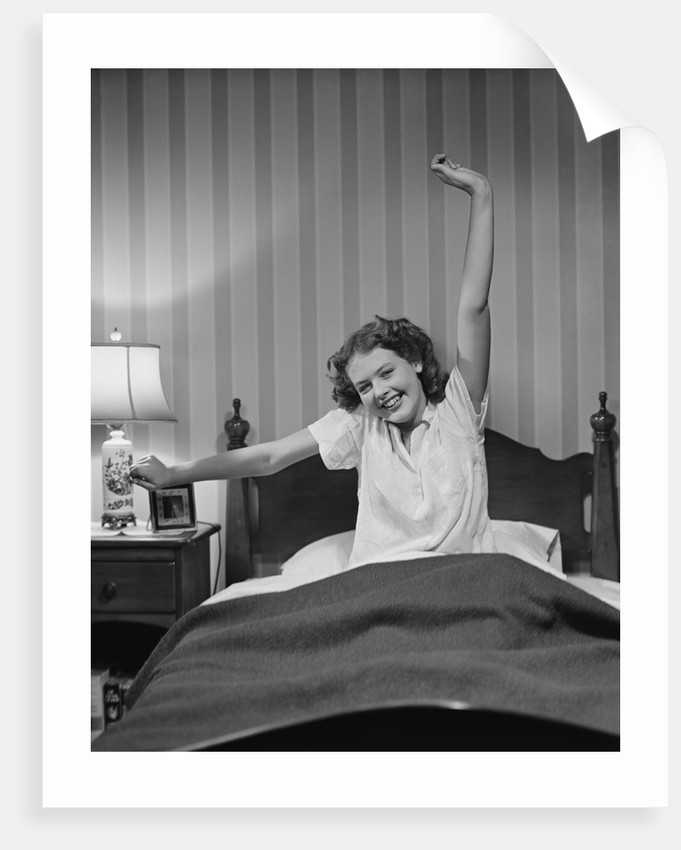 Young woman in bed stretching waking up by Corbis