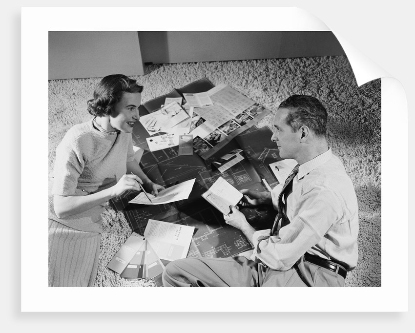 Couple man woman sitting floor looking at plans for new house by Corbis