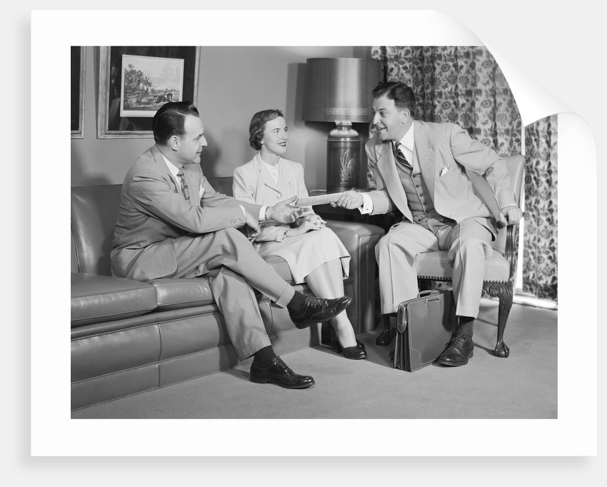 Couple sitting on couch talking to smiling insurance salesman handing them a policy by Corbis