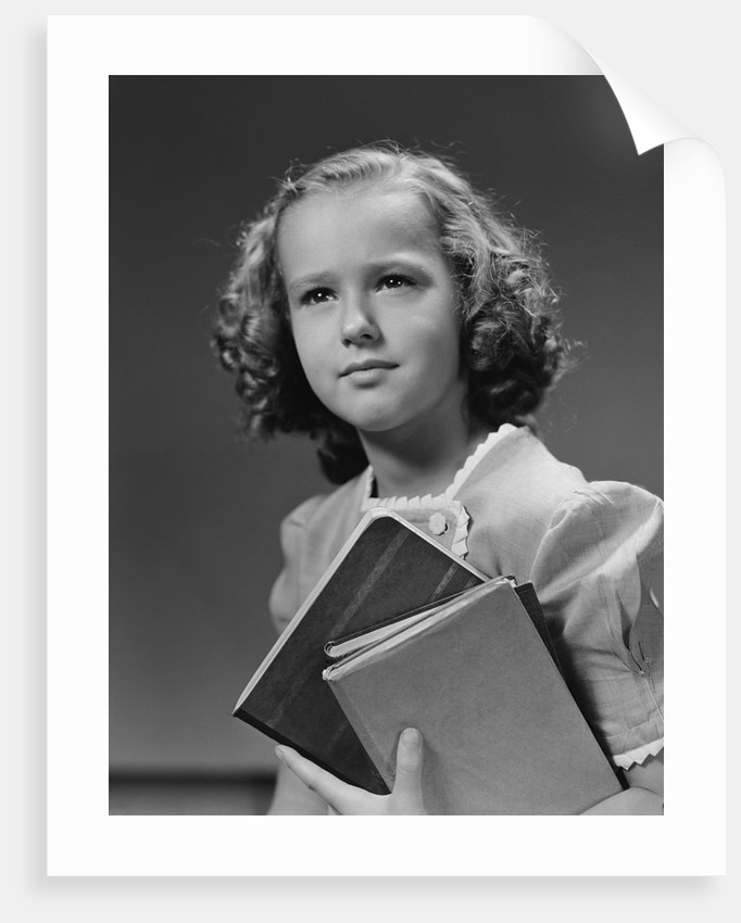 Portrait serious girl student holding school books by Corbis