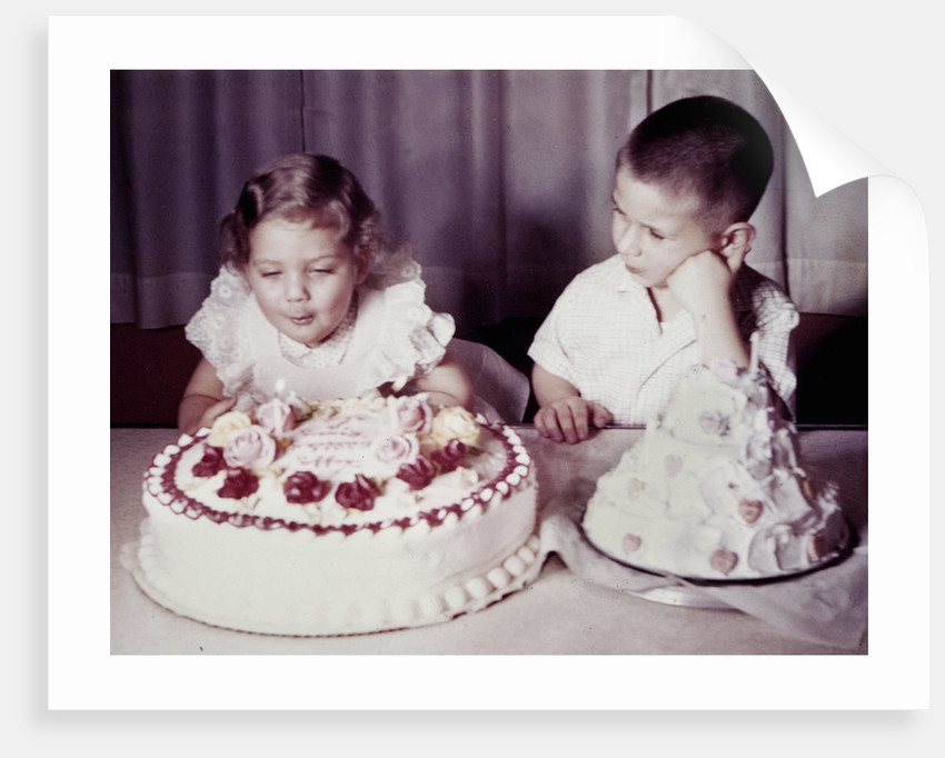 Brother watches his sister blow out candles on birthday cake, ca. 1956 by Corbis