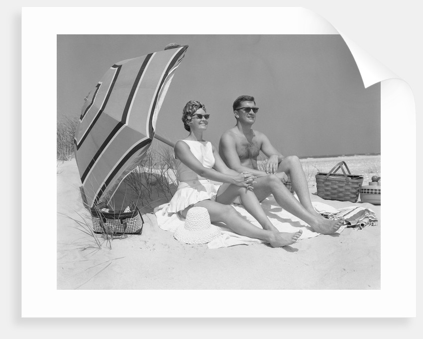 1960s couple in sunglasses sitting on beach blanket with legs extended with umbrella by Corbis