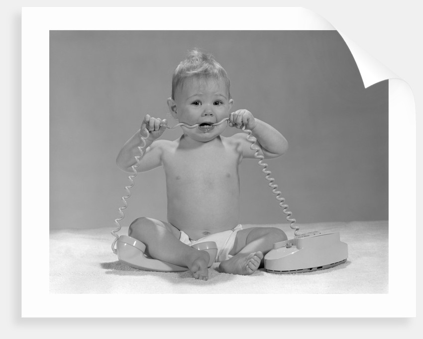 1960s blond baby sitting up looking at camera chewing on telephone cord by Corbis