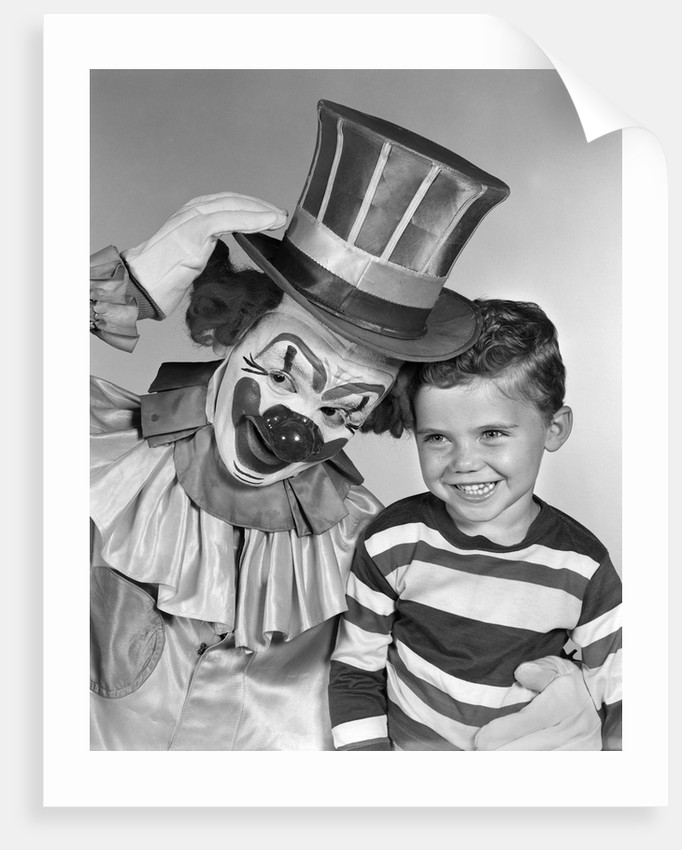 1950s smiling clown with top hat arm around grinning boy in striped shirt by Corbis