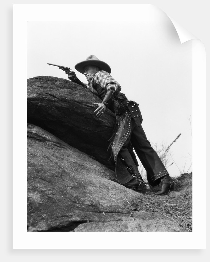 1920s cowboy among rocks aiming revolver by Corbis