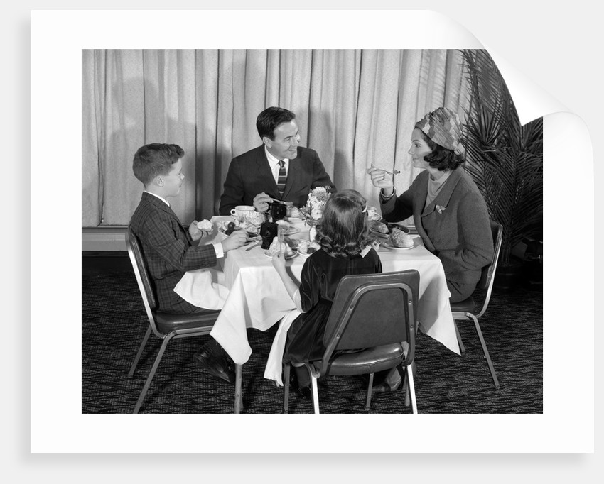 1960s smiling happy family of four eating meal in restaurant dad talking to mom who is wearing turban style hat by Corbis