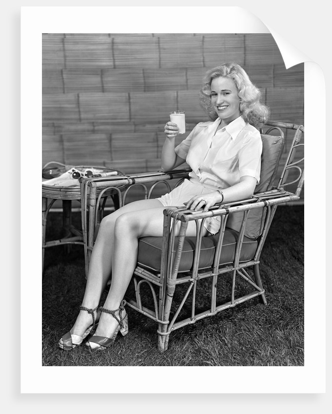 1940s blonde woman in bamboo chair holding up glass of milk smiling wearing white shorts looking
