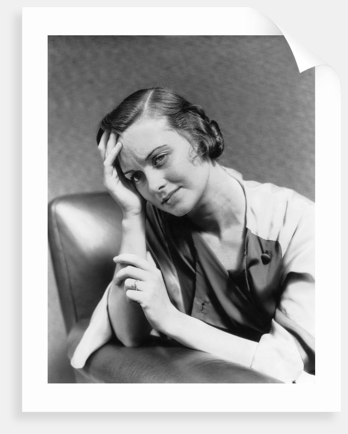 1930s 1940s woman sitting in chair worried sad expression one hand up to her forehead by Corbis