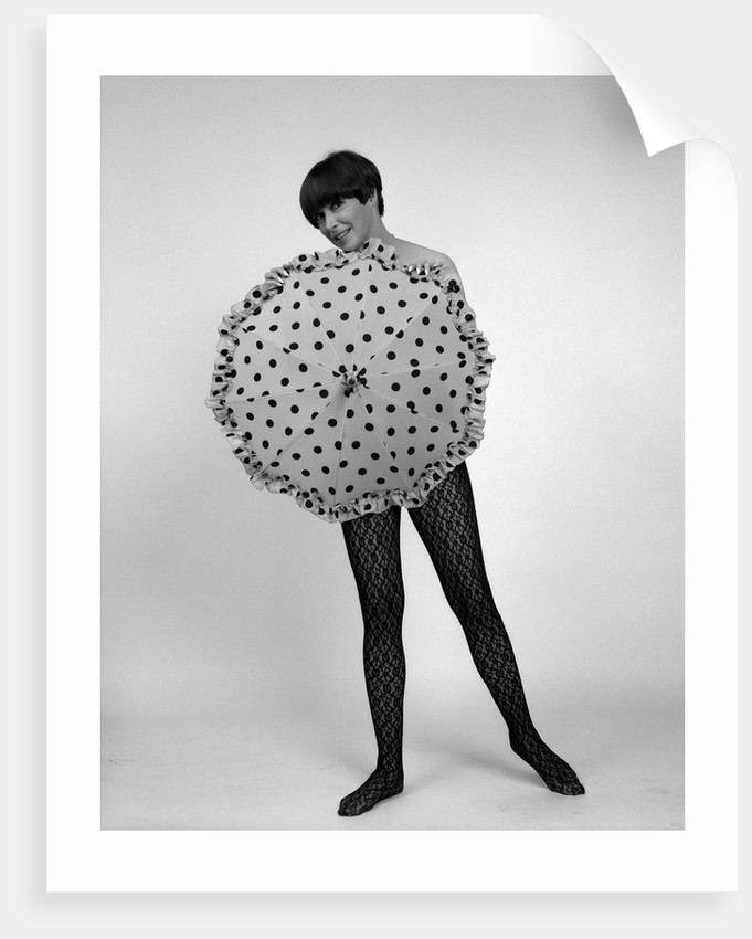 1960s full-length portrait of short- haired brunette in lacy hose covering naked torso with polka-dotted umbrella by Corbis