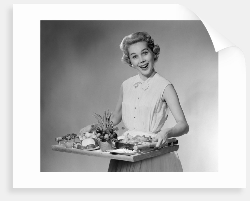 1950s woman looking at camera smiling holding platter of hors d'oeuvres snacks by Corbis