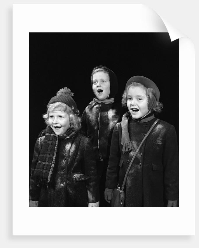 1940s three children singing caroling by Corbis