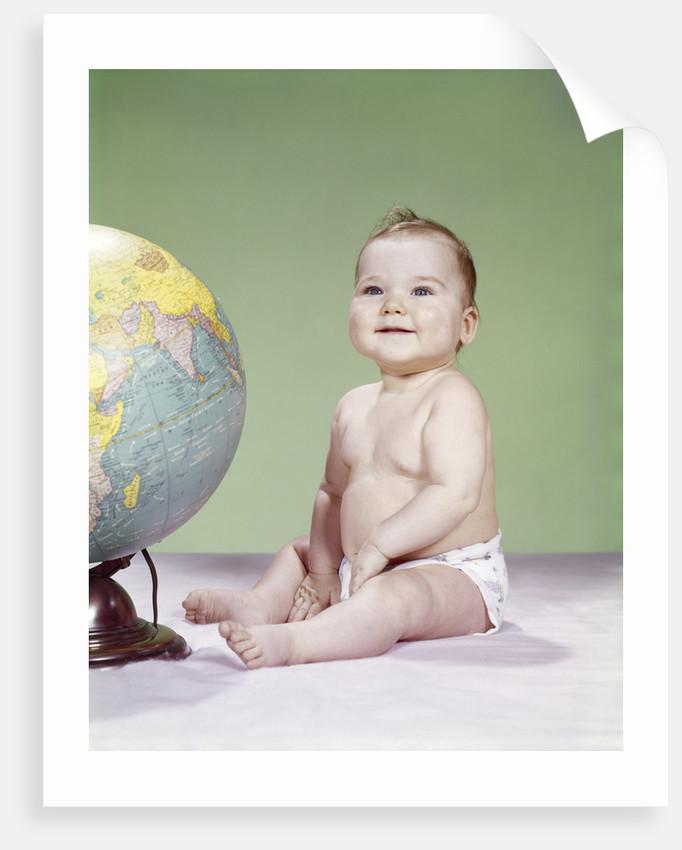 1960s smiling baby wearing diaper sitting beside earth globe