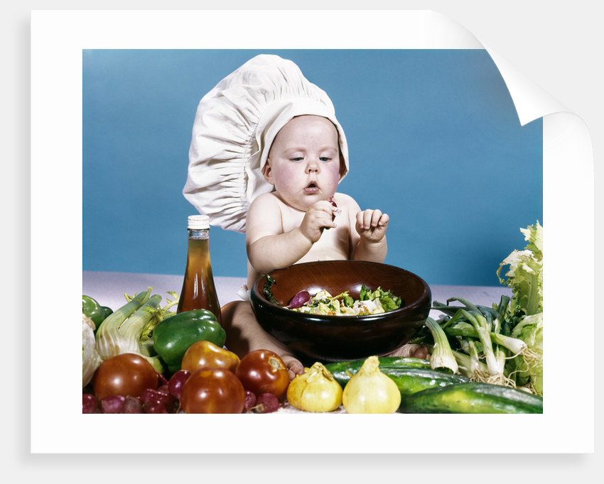 0aaee984abd 1960s baby making salad wearing chef hat with variety of fresh ingredients  vegetables by Corbis
