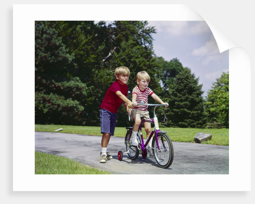 1960s 1970s boy helping little brother ride two wheel bicycle with training wheels by Corbis
