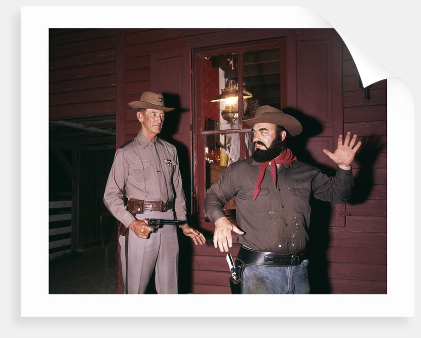 1960s 1970s western sheriff arrests bearded cowboy about to draw gun by Corbis