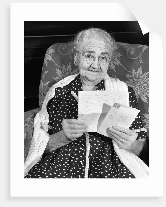 1960s elderly woman in polka-dotted dress & shawl reading letter by Corbis