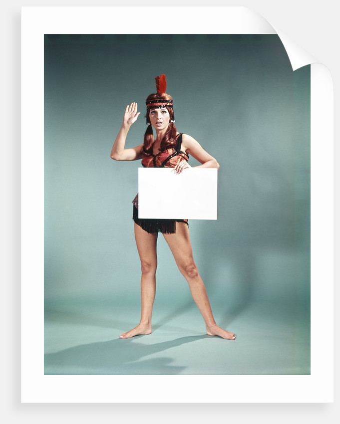 1960s 1970s Character Woman Wearing Native American Feather Headdress Making How Gesture Holding Blank Sign Looking At Camera by Corbis