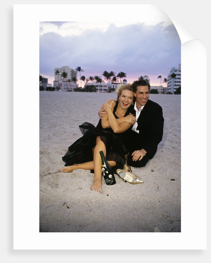 1990s Laughing Couple Man Woman In Formal Wear Sitting Hugging On Beach by Corbis