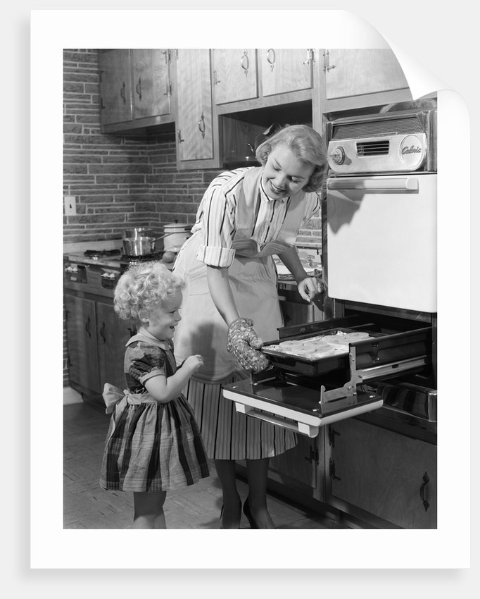 1950s Smiling Mother Daughter In Kitchen Broiling Pork Chops by Corbis