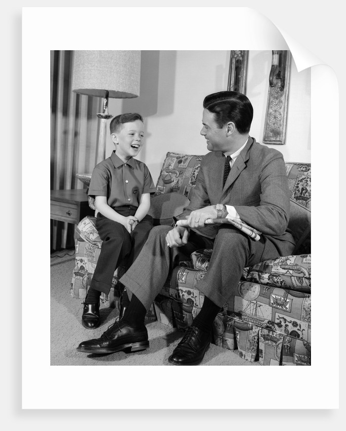 1960s boy sitting on couch smiling laughing talking with dad by corbis