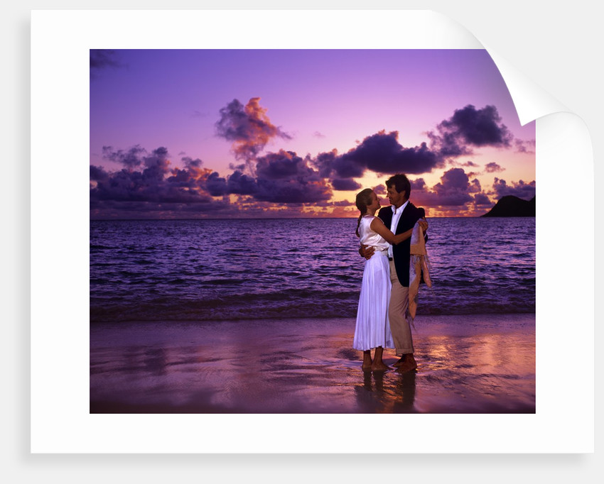 Dressed up couple embracing on the beach at sunset by Corbis