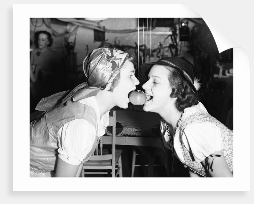 Girls Biting into Hanging Apple by Corbis