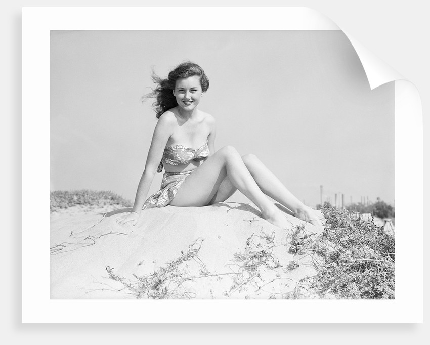 Young Woman Seated on Sand Dune by Corbis