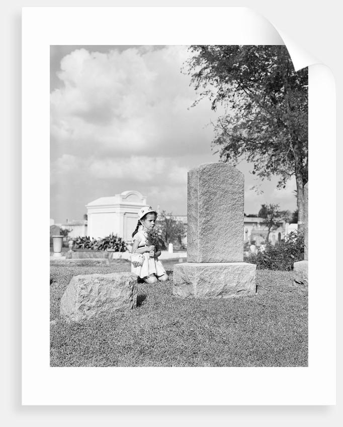 Girl Kneels at Headstone by Corbis