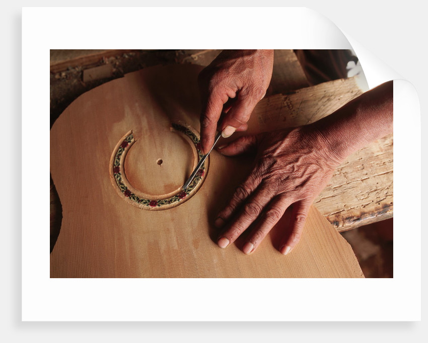 Carving a Guitar Face by Corbis