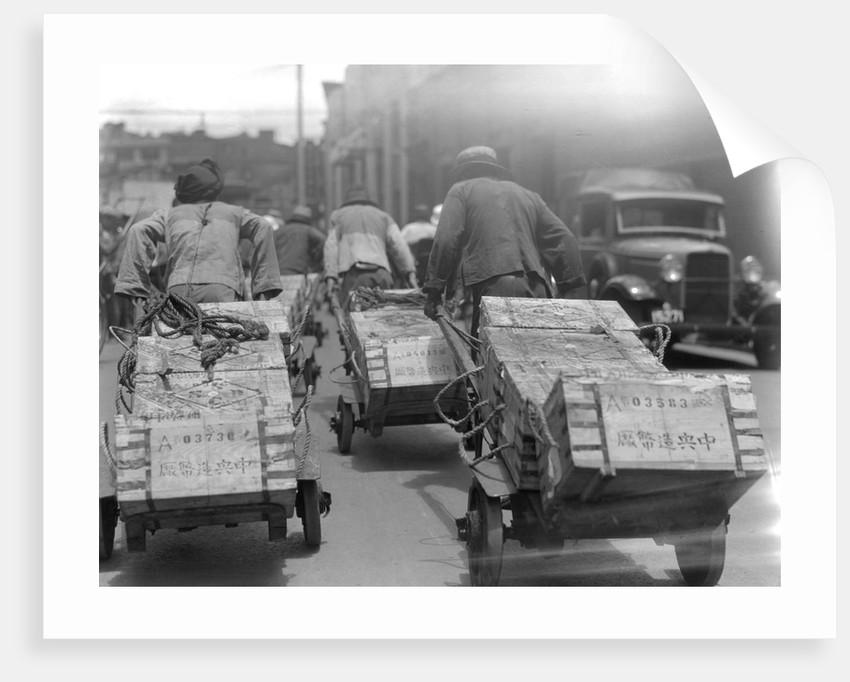 Chinese Men Pulling Heavy Loads of Silver Bullion by Corbis