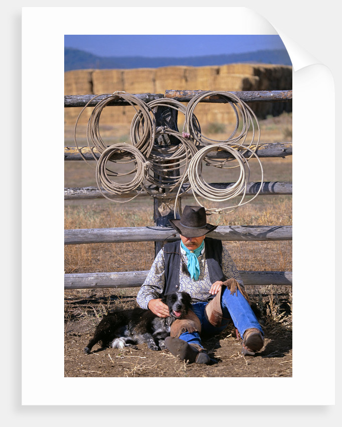 Cowboy and Dog Sitting Against Fence by Corbis