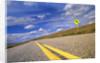 Curving rural highway under cumulus clouds in Colorado prairie by Corbis