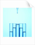 A glass pipette drops water in to a series of staggered test tubes or vials by Corbis