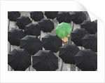 Green umbrella among group of black by Corbis