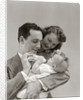 1940s Father Cradling Baby Daughter Feeding Her Bottle With Mother Looking Over His Shoulder by Corbis