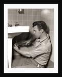 1950s Man Plumber Fixing Bathroom Sink by Corbis