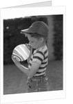 1950s Side View Of Boy In Baseball Cap and Striped T-Shirt Blowing Up Swirled Balloon by Corbis