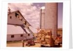 1970s Girl Watching Hay Bales On Conveyor Belt Loading Into Barn By Farm Grain Silos by Corbis